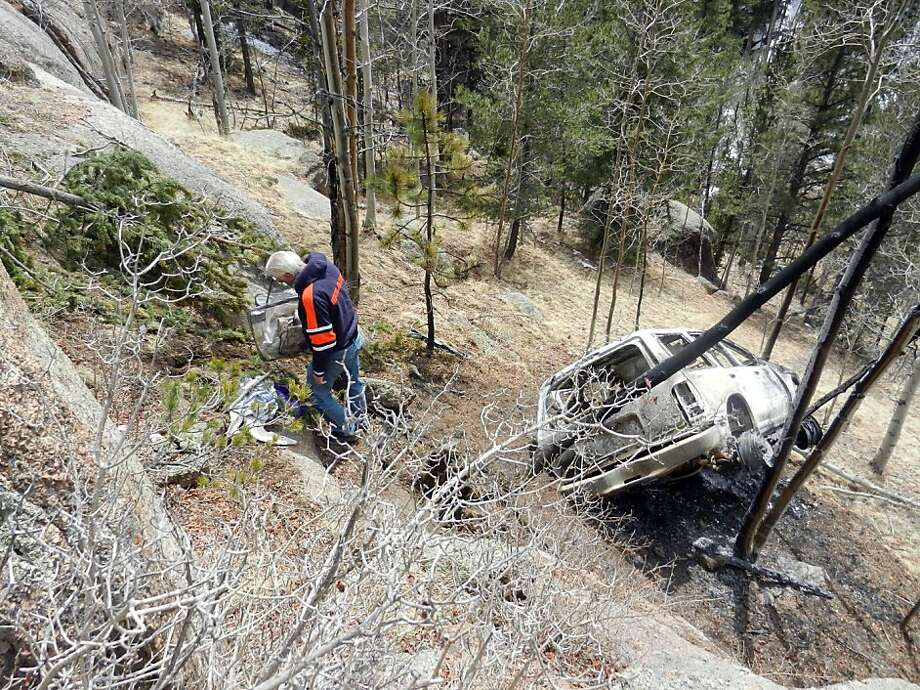 Six-hour ordeal in the Colorado woods: Craig Landals, boyfriend of Sandy Mileto, inspects the wreckage of Mileto's Jeep on a hillside off Colorado 67 