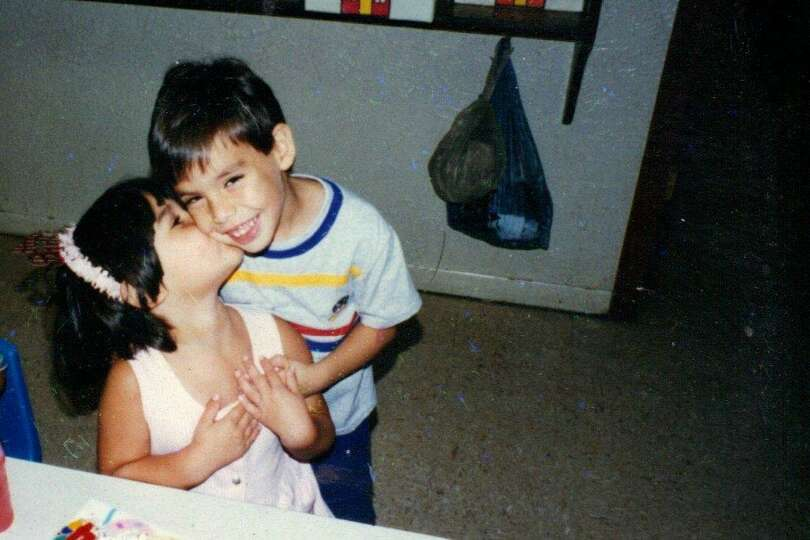 Then: 1996, Anna Becerra, 2, gives her brother Kevin, 3, a kiss on the cheek.