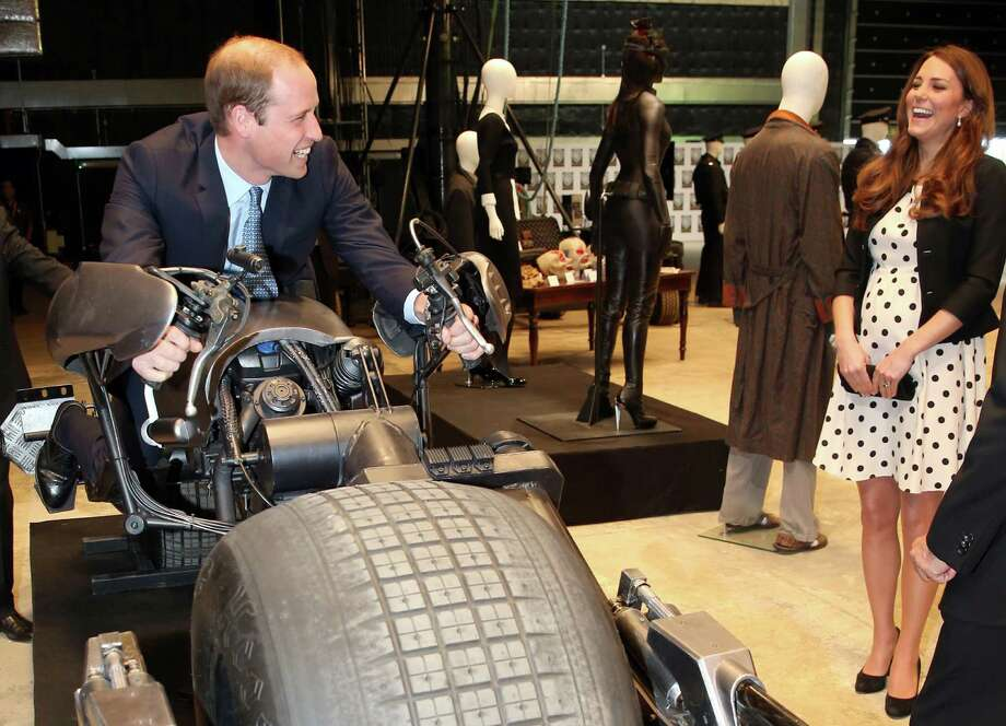 """Britain's Kate the Duchess of Cambridge watches her husband Prince William as he sits on the 'Batpod' during the inauguration of """"Warner Bros. Studios Leavesden"""" near Watford, approximately 18 miles north west of central London, Friday, April 26, 2013. As well as attending the inauguration Friday at the former World War II airfield site, the royals will undertake a tour of Warner Bros. """"Studio Tour London - The Making of Harry Potter"""", where they will view props, costumes and models from the Harry Potter film series. (AP Photo/Chris Jackson, Pool) Photo: Chris Jackson"""