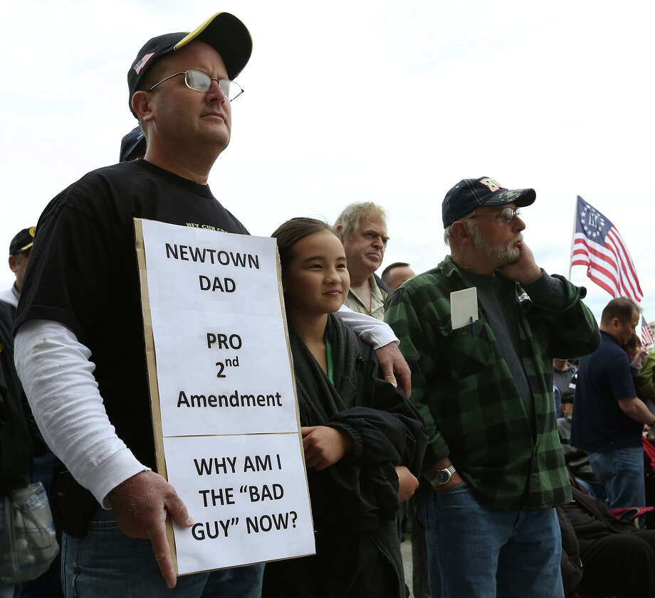Bill Stevens  of Newtown, Conn.  and his daughter Victoria, 10, listen to the speakers during a gun rights rally  at the Connecticut  State Capitol. Photo: Jared Ramsdell, MBO / Journal Inquirer