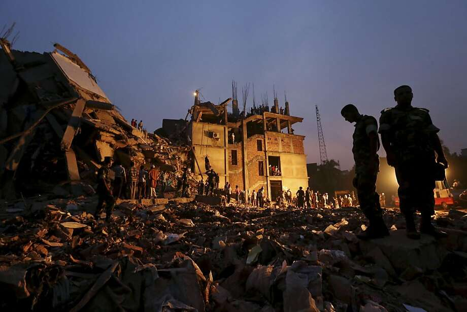 Bangladeshi soldiers stand in the rubble at the site of a building that collapsed Wednesday in Savar, near Dhaka, Bangladesh, Friday, April 26, 2013. By Friday, the death toll reached at least 270 people as rescuers continued to search for injured and missing, after a huge section of an eight-story building that housed several garment factories splintered into a pile of concrete.  Photo: Kevin Frayer, Associated Press