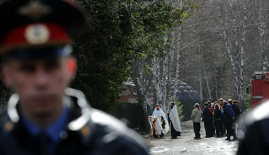 Orthodox  priests conduct service in front of the burned psychiatric hospital in the small town of Ramensky around 40 kilometres (25 miles) outside Moscow, on April 26, 2013. Thirty-eight people, mostly psychiatric patients, were killed in a fire that raged today at a psychiatric hospital in the Moscow region, trapping the inmates inside behind barred windows.  Photo: Andrey Smirnov, AFP/Getty Images