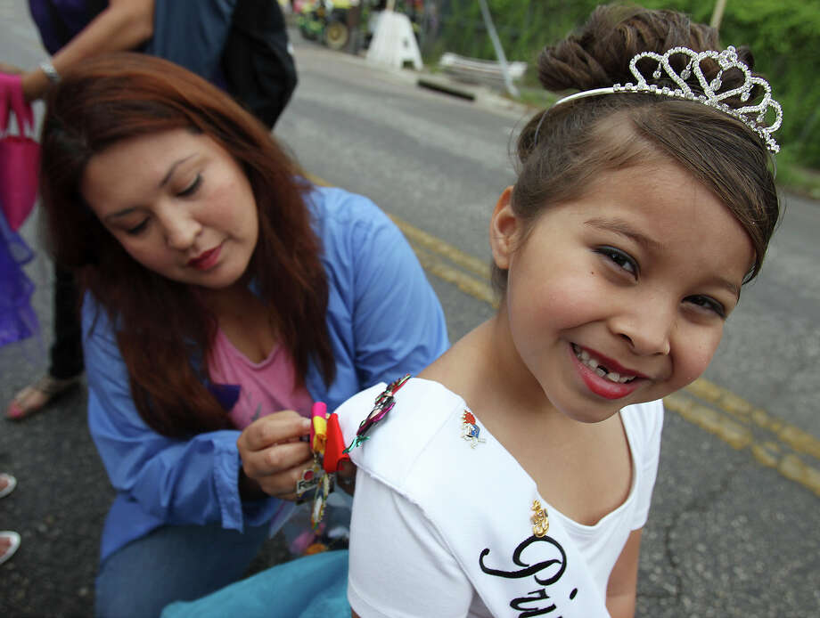 Gabby Duran smiles as her mother, Sharon, pins fiesta medals onto her sash before the start of the Battle of Flowers Parade on Friday, Apr. 26, 2013. Photo: Kin Man Hui, San Antonio Express-News / © 2013 San Antonio Express-News