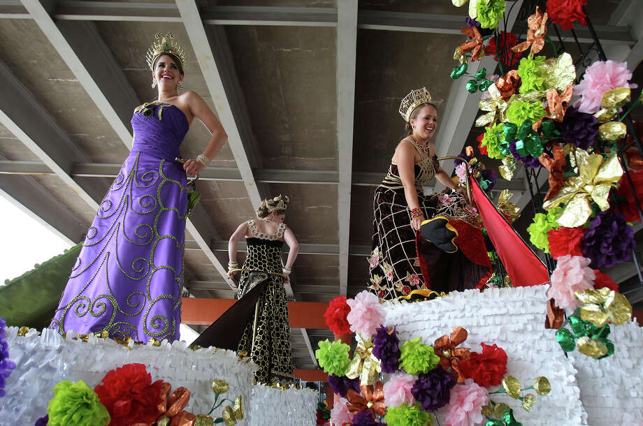 Duchesses Grace Dewar (from left), Audrey Hicks and Jennifer Berg make their way to the top of their parade float before the start of the Battle of Flowers Parade on Friday, Apr. 26, 2013. Berg was adjusting her unique footwear after being lifted to the top of the float via a forklift. Photo: Kin Man Hui, San Antonio Express-News / © 2013 San Antonio Express-News
