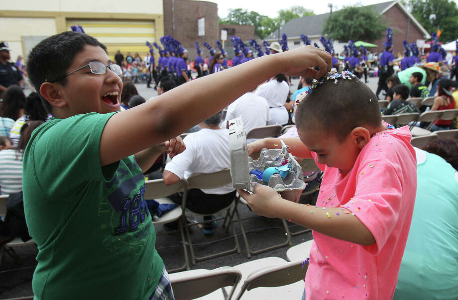 Joshua Martinez (left) cracks a cascarone over his little cousin, Jaiven Arredondo, during the Battle of Flowers Parade on Friday, Apr. 26, 2013. Photo: Kin Man Hui, San Antonio Express-News / © 2013 San Antonio Express-News