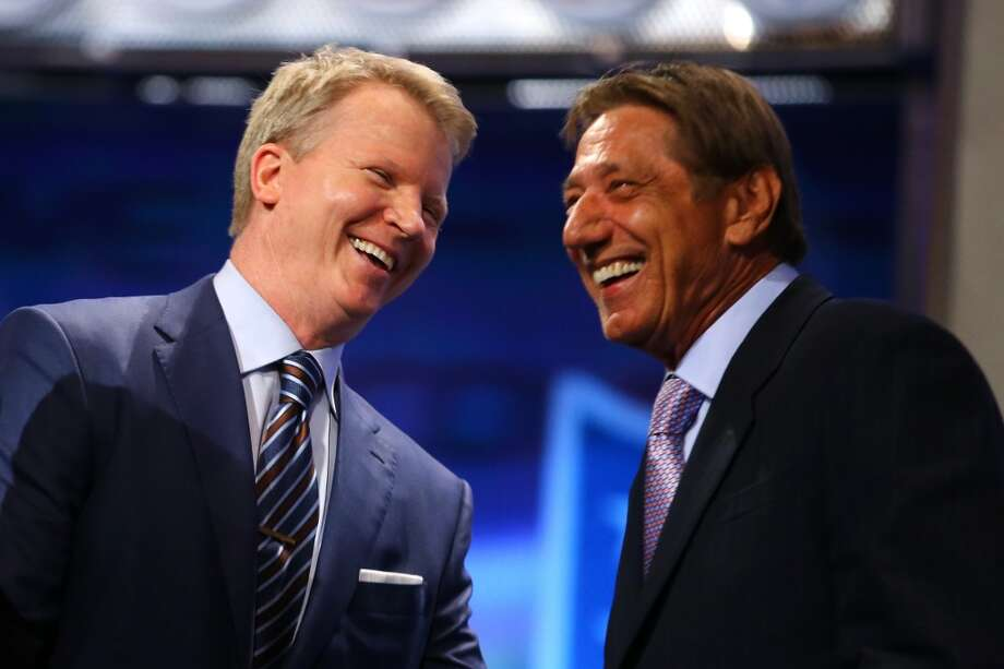 Former New York Giants quarterback Phil Simms and former New York Jets quarterback Joe Namath share a laugh on stage.