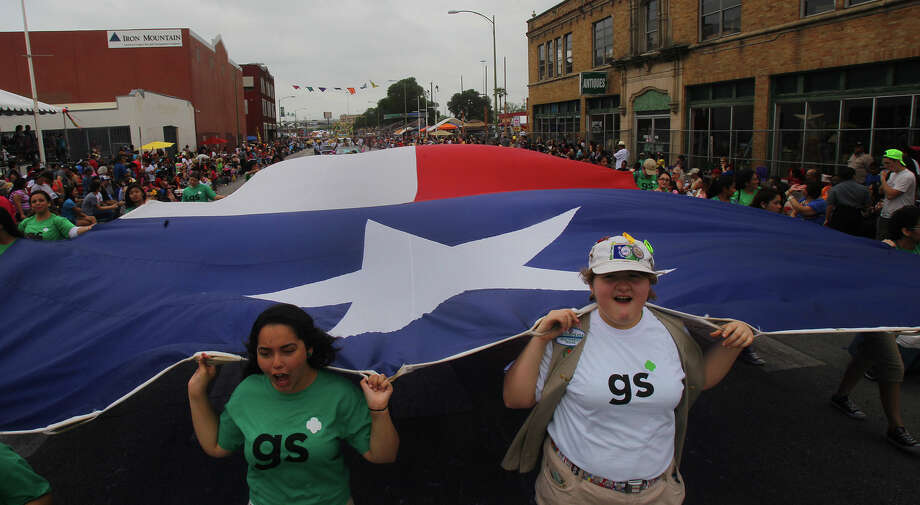 Girl Scouts band march down Broadway with a huge Texas flag Friday April 26, 2013 during the Battle of Flowers parade during the annual Fiesta celebration. Photo: JOHN DAVENPORT, SAN ANTONIO EXPRESS-NEWS / 490390