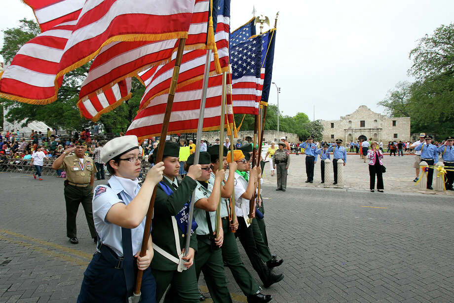 The vanquard of flags passes by the Alamo during as Battle of Flowers Parade moves through the downtown area  on  April 26 2013. Photo: TOM REEL