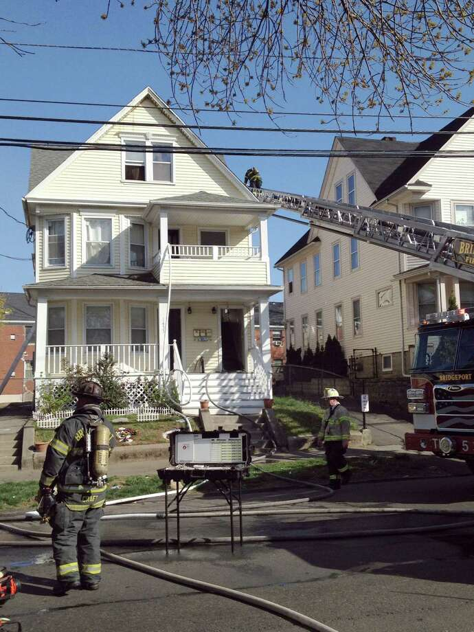 A fire in a multi-unit home on North Avenue displaced eight city residents on Friday. Photo: Denis O'Malley / Connecticut Post