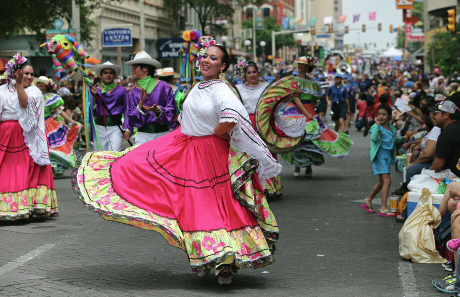 St. Edwards University Ballet Folklorico dancers perform on Commerce Street as the Battle of Flowers Parade moves through the downtown area  on  April 26 2013. Photo: TOM REEL, San Antonio Express-News / San Antonio Express-News