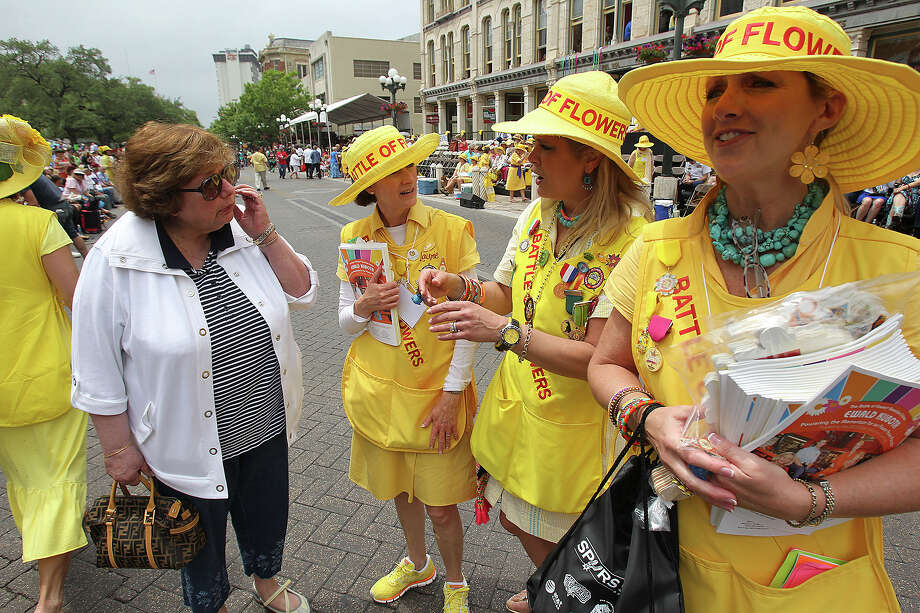 Carol Calta , from Cleveland, gets some help from Battle of Flowers Association workers (from left) Laurie Bracher, Karynn O'Connell and Becky Smith as the Battle of Flowers Parade moves through the downtown area  on  April 26 2013. Photo: TOM REEL