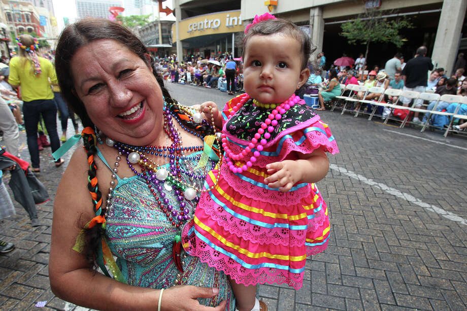 Aggie Jaramillo holds her grand daughter Natalia as the Battle of Flowers Parade moves through the downtown area  on  April 26 2013. Photo: TOM REEL