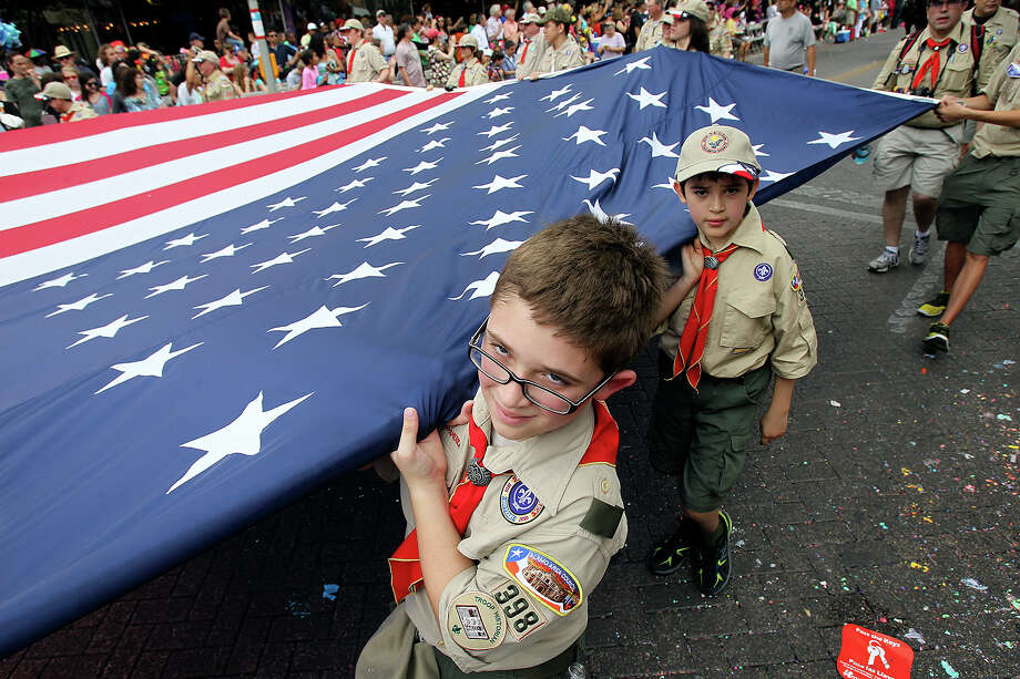 Scouts walk the U.S. flag through Alamo Plaza as the Battle of Flowers Parade moves through the downtown area  on  April 26 2013. Photo: TOM REEL