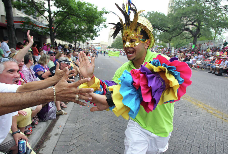 A member of Edison High School's Rio Carnival group slaps hands on Alamo Street as the Battle of Flowers Parade moves through the downtown area  on  April 26 2013. Photo: TOM REEL