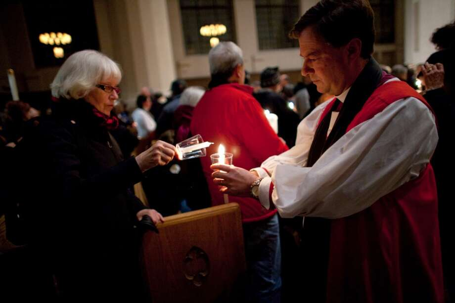 Episcopal Bishop Greg Rickel lights candles at St. Marks Cathedral during an interfaith vigil and march against gun violence on Saturday, February 9, 2013 in Seattle. Hundreds of people marched with candles from St. Marks Episcopal Cathedral, through Capitol Hill and eventually to St. James Catholic Cathedral. (Joshua Trujillo, seattlepi.com) Photo: SEATTLEPI.COM