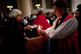 Episcopal Bishop Greg Rickel lights candles at St. Marks Cathedral during an interfaith vigil and march against gun violence on Saturday, February 9, 2013 in Seattle. Hundreds of people marched with candles from St. Marks Episcopal Cathedral, through Capitol Hill and eventually to St. James Catholic Cathedral. (Joshua Trujillo, seattlepi.com)