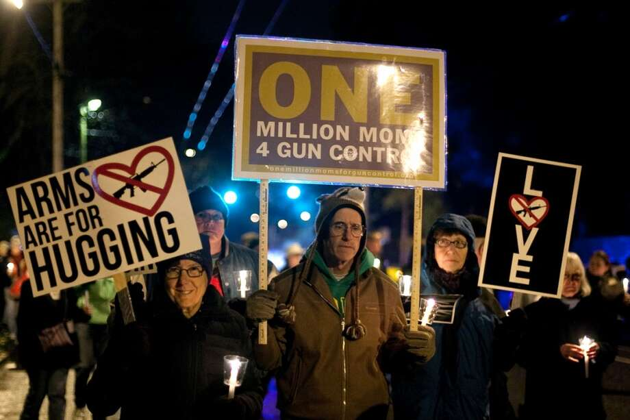 Participants carry signs during an interfaith vigil and march against gun violence on Saturday, February 9, 2013 in Seattle. Hundreds of people marched with candles from St. Marks Episcopal Cathedral, through Capitol Hill and eventually to St. James Catholic Cathedral. (Joshua Trujillo, seattlepi.com) Photo: SEATTLEPI.COM