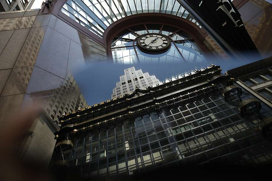 The front of San Francisco's rehabilitated Hallidie Building, center, is seen reflected in an iPhone on Friday. The building underwent rehabilitation to repair the decorative sheet metal frieze panels and cornices, balconies, and fire escapes and repainted in its original blue and gold. It is believed to be the first American building to feature a glass curtain wall. Photo: Lea Suzuki, The Chronicle