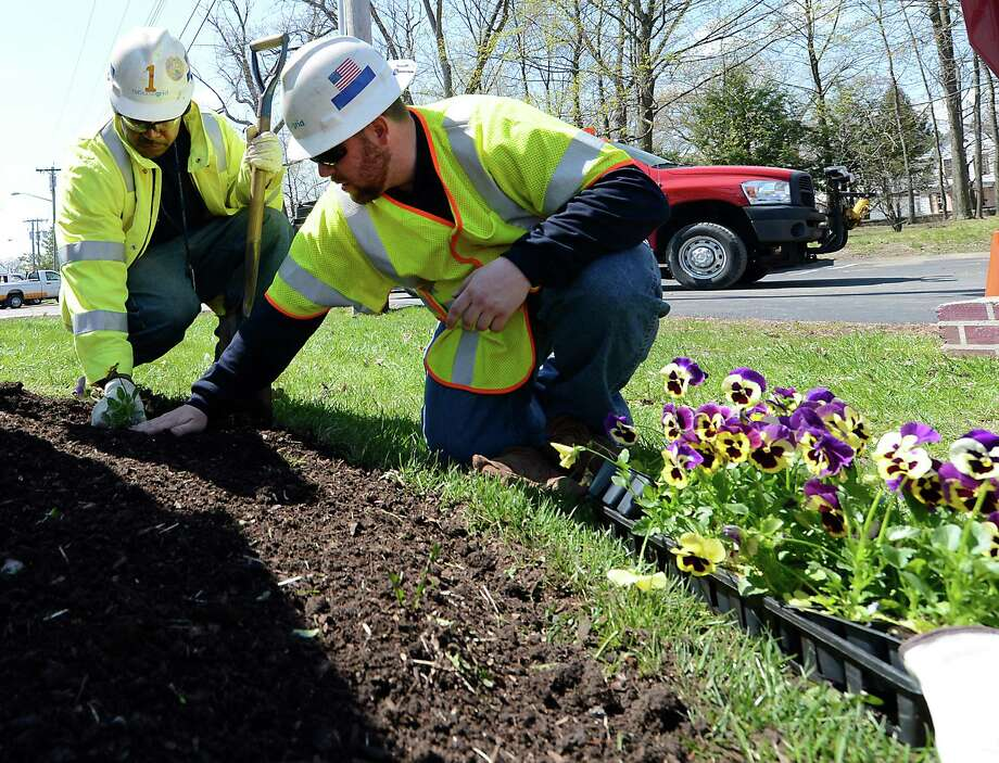 National Grid volunteers Floyd Harris, cable splicer, left, and Make Tedford, right plant flowers as they help get Parsons Child & Family center ready for spring in honor of Earth Day April 26, 2013 in Albany, N.Y.  The volunteers did a massive clean-up and planting at the Center.   (Skip Dickstein/Times Union) Photo: SKIP DICKSTEIN