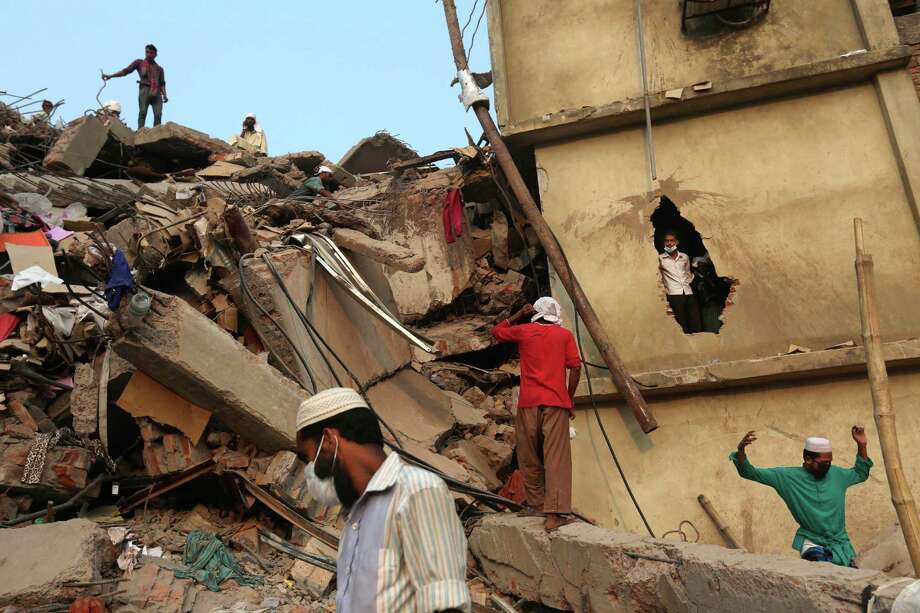 Bangladeshi rescue workers search the rubble at the site of a building that collapsed Wednesday in Savar, near Dhaka, Bangladesh, Friday, April 26, 2013. The death toll reached hundreds of people as rescuers continued to search for injured and missing, after a huge section of an eight-story building that housed several garment factories splintered into a pile of concrete.(AP Photo/Kevin Frayer) Photo: Kevin Frayer