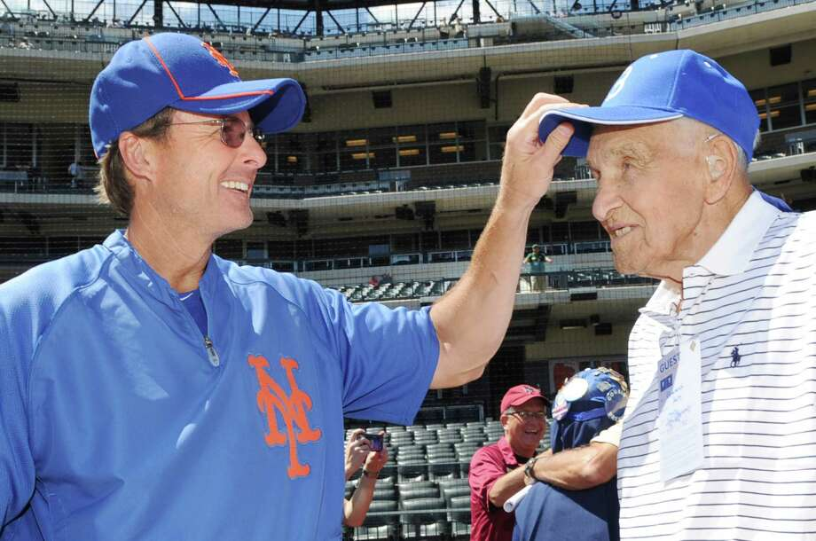 New York Mets third base coach Tim Teufel, a Greenwich native, playfully touches the Brooklyn Dodgers cap of Mike Sandlock, 96, a native of Old Greenwich, Conn., the oldest living former Brooklyn Dodgers player, on the field during batting practice before the Los Angeles Dodgers-New York Mets baseball game on Saturday, July 21, 2012, at Citi Field in New York. Photo: Bob Luckey / Greenwich Time