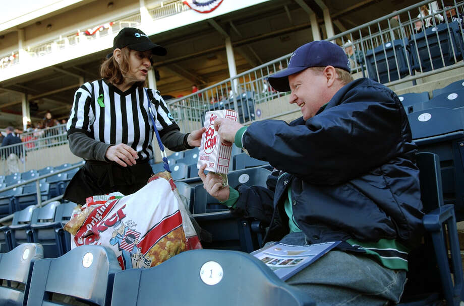 Bluefish fan Jim Simpson, of Stratford, buys some popcorn from vendor Holly Ziem, at the team's home opener against the York Revolution at the Ballpark at Harbor Yard in Bridgeport, Conn. on Friday April 26, 2013. Photo: Christian Abraham / Connecticut Post