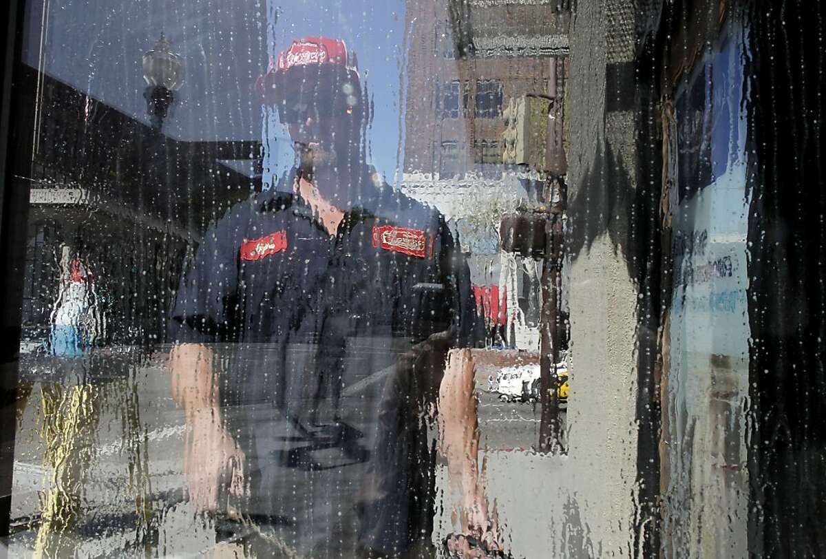 Ryan Beverage, who works works for a sign company wets down a window to hang advertising at a business along Shattuck Ave, on Tuesday April 23, 2013, in Berkeley, Ca. The City of Berkeley is considering raising the minimum wage from $8 to $10.55 an hour.