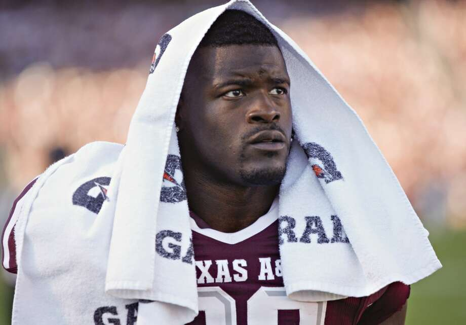 Christine Michael (33) of the Texas A&M Aggies is led off the field after being ejected for striking a player after the play against the Sam Houston State Bearkats at Kyle Field in College Station, Texas, on Nov. 17, 2012.