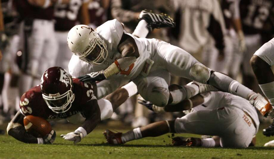 Tailback Christine Michael (33) of the Texas A&M Aggies loses control of the ball as the Texas Longhorns defense pursues in the second half at Kyle Field in College Station, Texas, on Nov. 26, 2009.