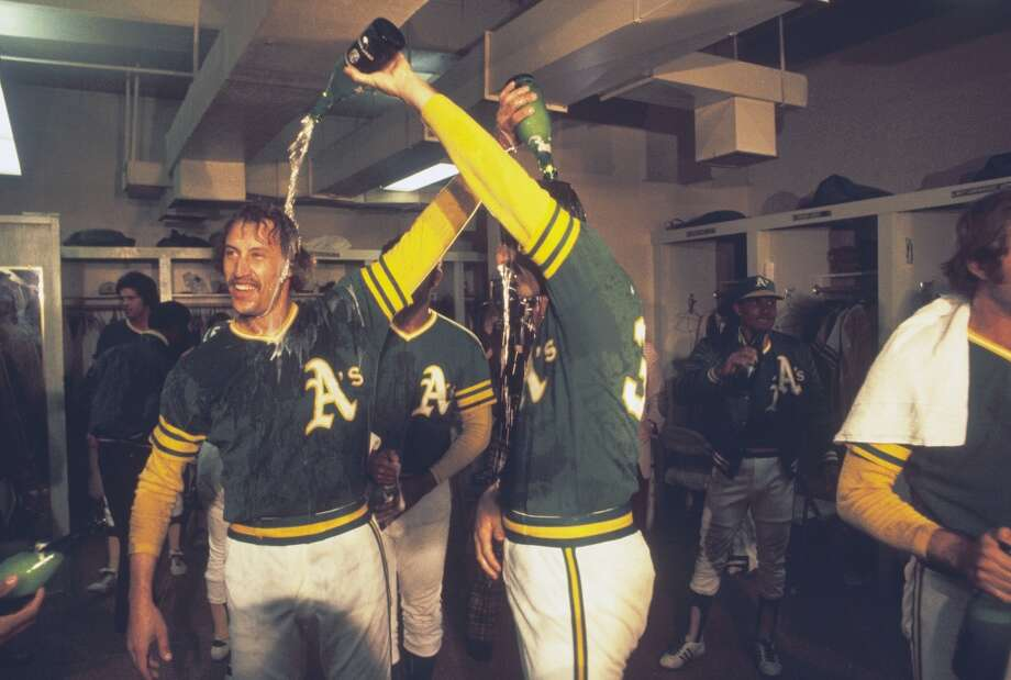 Oakland Athletics' Ken Holtzman #30 and Rollie Fingers #34 celebrate in the clubhouse after defeating the Baltimore Orioles to win the American League Championship Series at Oakland-Alameda County Coliseum on October 11, 1973 in Oakland, California. The Athletics defeated the Orioles 3-0 in game 5, the final game of the series.