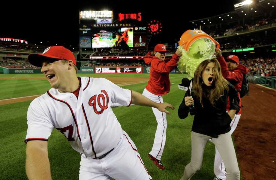 Washington Nationals starting pitcher Jordan Zimmermann dodges the Gatorade, but MASN's sideline reporter Julie Alexandria, wasn't so lucky as relief pitchers Drew Storen, and Ryan Mattheus dump the Gatorade, after a baseball game against the Cincinnati Reds at Nationals Park Friday, April 26, 2013, in Washington. Zimmermann threw a one hit complete game shutout and the Nationals won 1-0. (AP Photo/Alex Brandon) Photo: Alex Brandon, Associated Press / AP