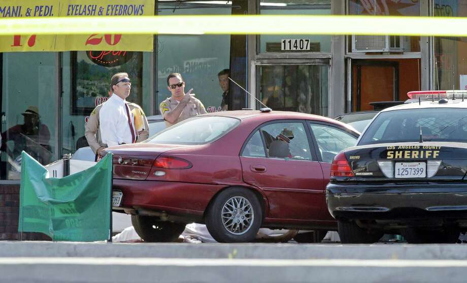 Los Angeles County Sheriff's investigators view the scene of a confrontation between a deputy and a civilian at a strip mall in the unincorporated Athens area of South Los Angeles Friday, April 26, 2013. A deputy was reportedly struck and injured by a man driving the red car, center, which has collided with the cruiser at right. The driver was then shot to death by another deputy.  His covered body is behind the red car. (AP Photo/Reed Saxon) Photo: Reed Saxon, Associated Press / AP