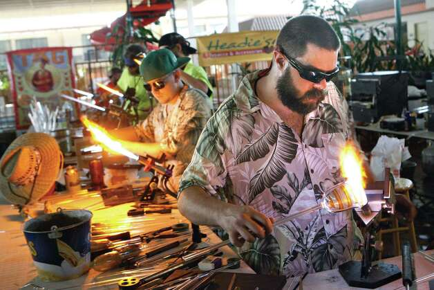 Brandon Welk, right, of Montage glass studio in Spokane, works on a wine glass during a glassblowing competition, Friday, April 26, 2013  at the first Tri-Cities Flame Off at the M Hotel in Richland, Wash.  (AP Photo/The Tri-City Herald, Kai-Huei Yau) Photo: Kai-Huei Yau, Associated Press / Tri-City Herald