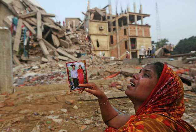 A Bangladeshi woman weeps as she holds a picture of her and her missing husband as she waits at the site of a building that collapsed Wednesday in Savar, near Dhaka, Bangladesh, Friday, April 26, 2013. The death toll reached hundreds of people as rescuers continued to search for injured and missing, after a huge section of an eight-story building that housed several garment factories splintered into a pile of concrete.(AP Photo/Kevin Frayer) Photo: Kevin Frayer, Associated Press / AP
