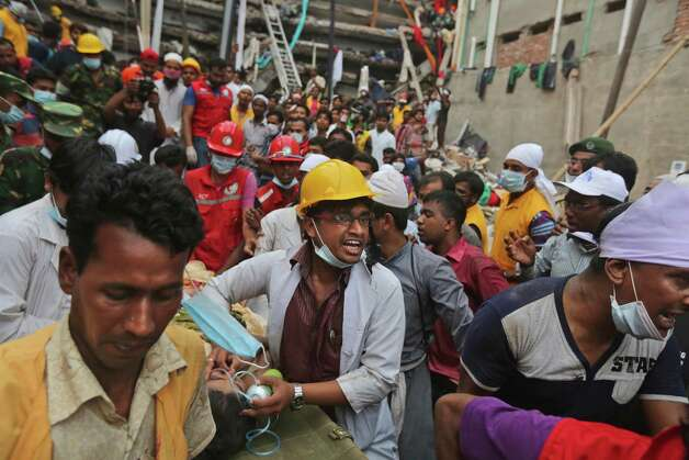 A Bangladeshi garment worker who was pulled alive from the rubble Friday April 26, 2013, is rushed on a stretcher from the site of a building that collapsed Wednesday in Savar, near Dhaka, Bangladesh. (AP Photo/Kevin Frayer) Photo: Kevin Frayer, Associated Press / AP