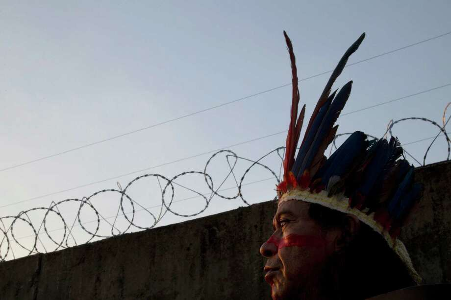 An Indian man watches as Brazilian police create a cordon around the Maracana stadium during a protest against the privatization of the stadium and planned demolition of the indigenous museum located nearby, in Rio de Janeiro, Brazil, Friday, April 26, 2013. Protestors are against the privatization of the stadium because it will lead to the demolition of the museum and a public school.  (AP Photo/Silvia Izquierdo) Photo: Silvia Izquierdo, Associated Press / AP
