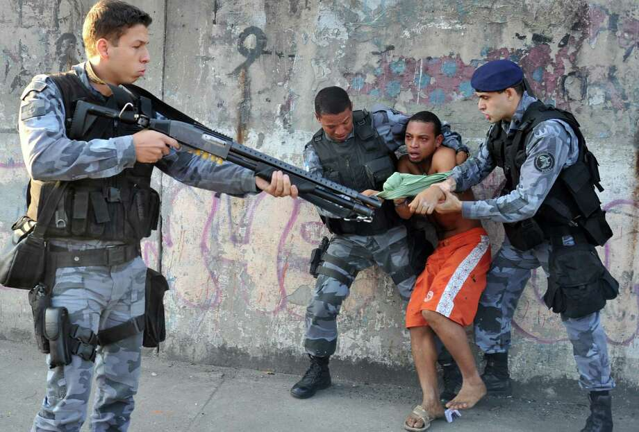 Officers of Rio de Janeiro's shock police battalion arrest a demonstrator after a group of natives returned to occupy Rio's former Indian Museum, on April 26, 2013. On March 22 the police forcibly ejected some 30 indigenous activists and supporters from the Indian Museum located next to the Maracana stadium, the venue for the 2014 World Cup final. Tgoverning body as part of an urban renewal program.  AFP PHOTO /TASSO MARCELO Photo: TASSO MARCELO, AFP/Getty Images / AFP