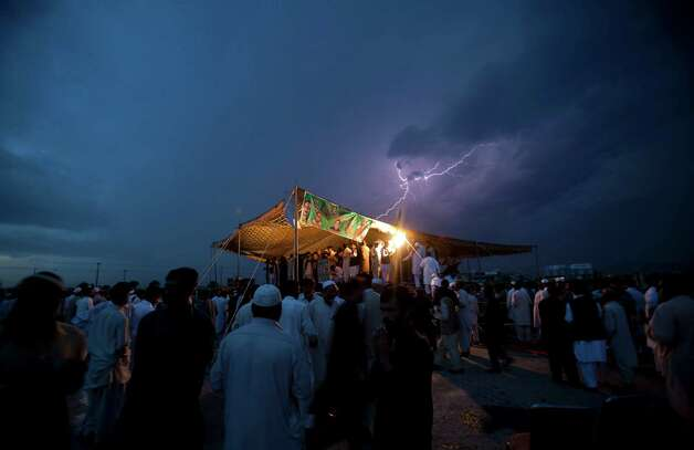 Lightning flashes as political supporters of the Pakistan Muslim League hold a meeting under tight security due to ongoing attacks on political rallies and parties' election offices, in Islamabad, Pakistan on Friday, April 26, 2013. The Muttahida Qaumi Movement has ordered the closure of election offices in Karachi following a blast that killed many party workers. (AP Photo/B.K. Bangash) Photo: B.K. Bangash, Associated Press / AP