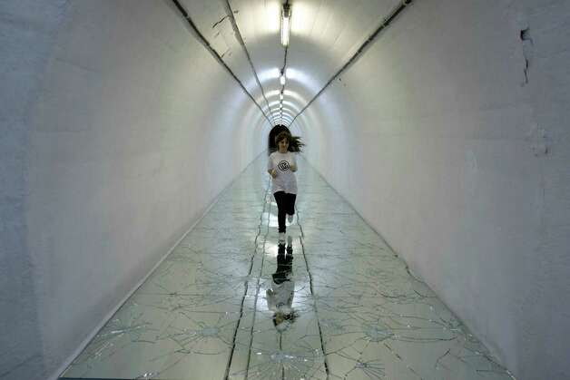 An official runs along a broken mirror art installation by Italian artist Alfredo Pirri as visitors tour contemporary art displayed at the war bunker, near town of Konjic, 80 kms south of Sarajevo, Bosnia, on Friday, April 26, 2013, as the once secret bunker, built to shelter Yugoslavia's Marshal Josip Broz Tito and the communist leadership from a nuclear war, turns for three months into one of the world's quirkiest contemporary art galleries. (AP Photo/Amel Emric) Photo: Amel Emric, Associated Press / AP