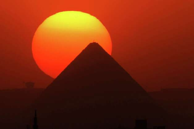 The sun sets behind the Great Pyramid in Giza, Egypt, Friday, April 26, 2013. Elsewhere, dozens of mostly masked protesters are hurling stones and firebombs in clashes with riot police at Egypt's presidential palace in a Cairo suburb.   (AP Photo/Amr Nabil) Photo: Amr Nabil, Associated Press / AP