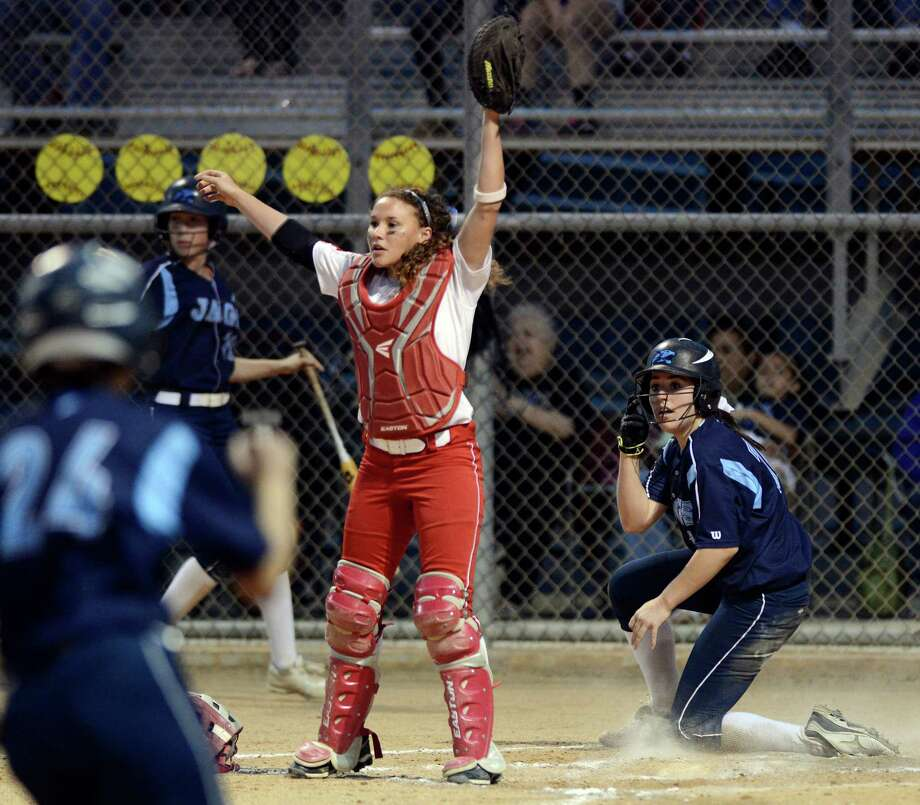 After a run by Johnson's Kate Weinman, right, Judson catcher Nicole Shedd, center, calls for the play at home as Johnson's Amber Hinkle, left, runs home, during a Class 5A bidistrict playoff high school softball game, Friday, April 26, 2013, at Steele High School in Cibolo, Texas. Photo: Darren Abate, Express-News