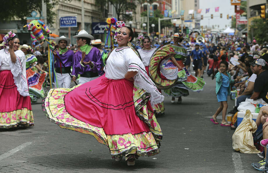 St. Edward's University Ballet Folklorico dancers perform on Commerce Street as the Battle of Flowers Parade makes its way from lower Broadway through downtown. Photo: Tom Reel / San Antonio Express-News