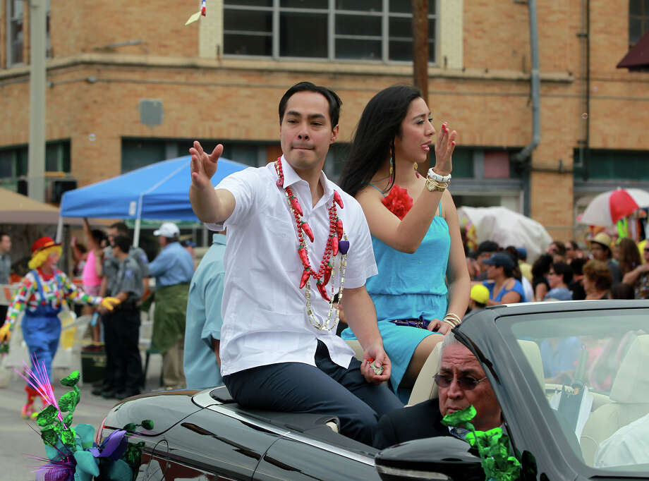 San Antonio Mayor Julian Castro tosses what appears to be a Fiesta medal (top, above hand) Friday April 26, 2013 during the Battle of Flowers parade. Seated on the right is his wife Erica Castro. Photo: SAN ANTONIO EXPRESS-NEWS / ©San Antonio Express-News/Photo may be sold to the public