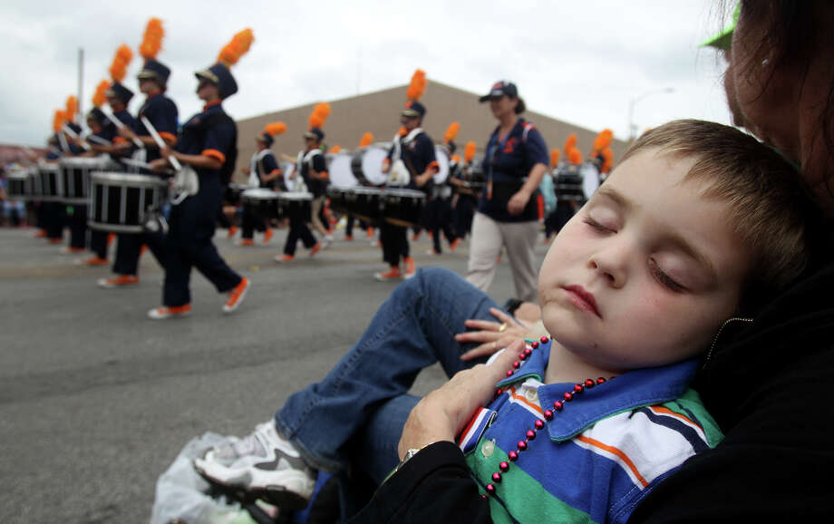 "Paul Brown,5, sleeps while drummers in a marching band pass by on Broadway during the 2013 Battle of Flowers parade. Brown was sleeping in the arms of his grandmother Dawn Brown. ""He's all partied out,"" Brown said. Photo: SAN ANTONIO EXPRESS-NEWS / ©San Antonio Express-News/Photo may be sold to the public"