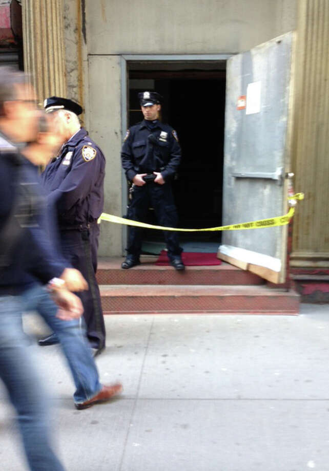 Crime scene tape and a New York City police officer block the service entrance to the site of a proposed Islamic community center in New York City, after a 5-foot-tall part has been discovered wedged between it and a luxury high-rise apartment building, Friday, April 26, 2013. The wreckage is believed to be from one of the hijacked planes destroyed in the Sept. 11, 2001 terrorist attacks on the World Trade Center. (AP Photo/Tom Hays) Photo: Tom Hays