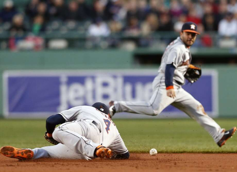 Brandon Laird of the Astros deflects the ball to teammate Jose Altuveon a single by Jacoby Ellsbury of the Red Sox.