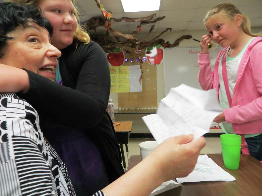 Navarro Intermediate School fifth-grader Cassie Wertheim hugs Inge Auerbacher after giving her a letter containing a 1943 penny, symbolizing the year Auerbacher was incarcerated in a Nazi concnetation camp. Looking on is student Cameron Royal. Photo: Zeke MacCormack / San Antonio Express-News