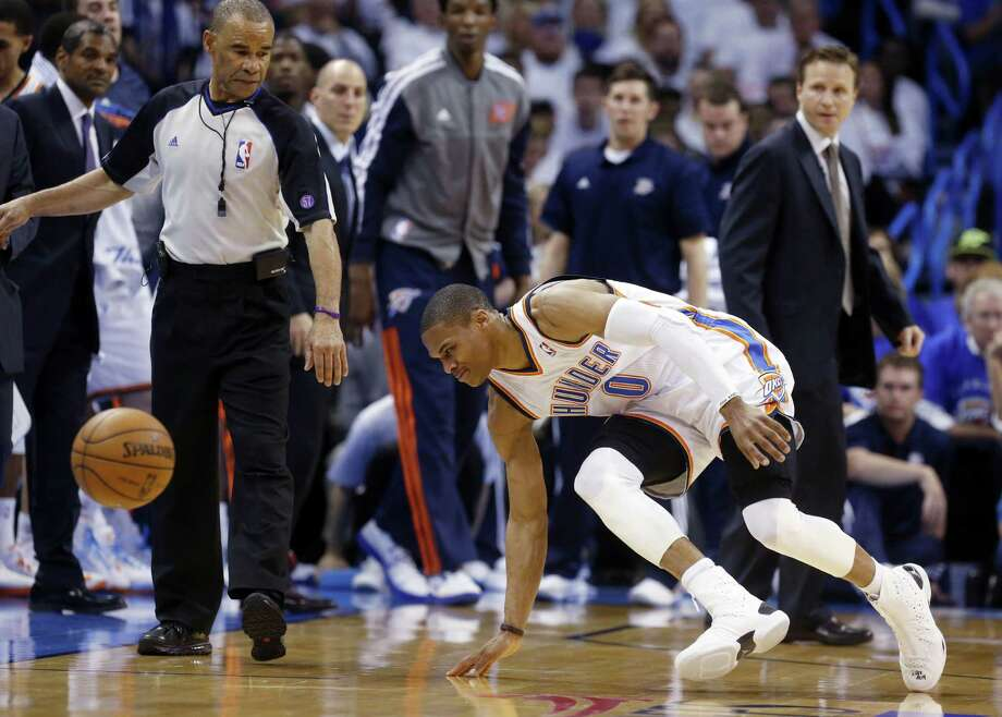 Thunder guard Russell Westbrook stumbles after hurting his right knee against the Rockets on Wednesday night. He will be out indefinitely. Photo: Sue Ogrocki / Associated Press