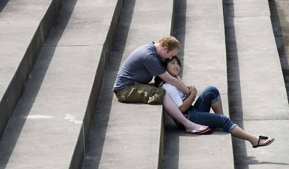Liam Talkington and Liz Richardson share the warm  weather on the banks of the Spokane River on the steps near the INB Performing Arts Center, r Friday, April 26, 2013 in downtown Spokane, Wash.  Photo: Dan Pelle, Associated Press