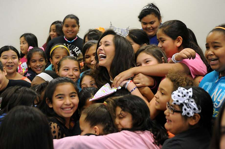 Miss Texas DaNae Couch, center, gets a group hug from the 4th-grade girls at Martinez Elementary School Friday, April 26, 2013, in Abilene, Texas. Couch spoke about gaining scholarship money to pay for law school, learning to twirl and answered questions about her lifestyle and footwear  Photo: Nellie Doneva, Associated Press